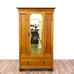 This armoire is featured in a solid wood with a glossy oak finish. This country farmhouse style wardrobe has a mirror, spacious bottom drawer, ample closet space, and brass hooks. Perfect for storing clothing! #countryfarmhouse #dressers #armoireorwardrobe #sandiegovintage #vintagefurniture
