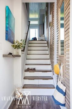 Beach cottage foyer features a blue abstract art piece hung above a floating wood shelf mounted beside a narrow white staircase fitted with storage drawers and stained wood treads complementing a wood handrail fixed opposite a wall lined with mirrors framed by a wood trim.
