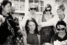 women praying over bride
