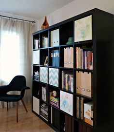 How to make the ikea expedit bookshelf look stylish AND useful for storage space. Hang 12 x 12 painted canvases in some of the cubbies....brilliant!