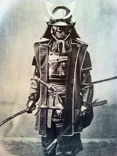 Samurai in full armor and wearing jinbaori (war coat). Photograph by Felice Beato.
