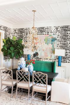 In this eclectic dining room from Kendall Simmons, bold black and white wallpaper becomes a chic backdrop for gold accents and vibrant furniture. Three dining chairs paired with a green buffet provide ample seats for guests at dinner parties.