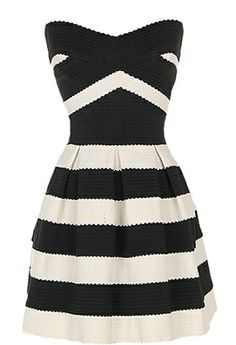 Retro Blast Dress: Features a subtle sweetheart neckline with crisscrossed textured bands to the front, gorgeous two-tone design with contrasting black and cream hues, high-volume A-line skirt, and an edgy exposed rear zipper to finish.