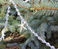 """Beach decor or nautical decor Christmas garland. This new coastal decor sparkly starfish garland is made with icy light blue beads with tons of maximum sparkle and shine. We add super cute and tiny 2"""" real white starfish to give it a lot of beautiful sweet coastal charm. Beads are heavy acrylic and just a barely-there ice blue plus silver spacer beads.  This blingy garland would be amazing on a white tree or mixed with white lights for extra blingy sparkle!  48"""" with hanging loops at both…"""