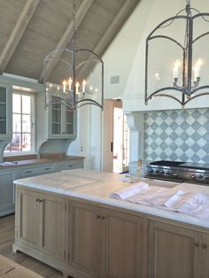 marble island with natural wood, iron lanterns,  then make other cabinets white....also like the ceiling.