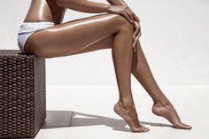 Beautiful woman tan legs. Against white wall. Stock Image