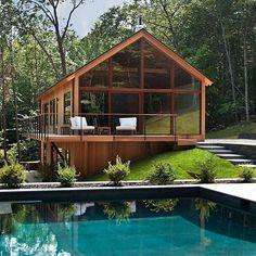 Casa em madeira com fechamento em vidro e piscina.