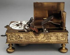 Mechanical alarm clock with flintlock candle lighting mechanism.   The flashpan of the mechanism was filled with gunpowder.  When the alarm sounded the cock would strike the frizzen, igniting the gunpowder which then would light the candle.  Originates from the early 18th century.