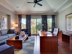 Decorated in blue, this lovely home office features hardwood flooring and a matching wood desk and coffee table. There's even a balcony nearby to catch a break from the work day.