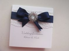Cameo wedding invitation with lace and satin ribbon. Shown in Navy blue