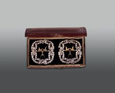 Shoe buckles in a leather case, Paris, mid 18th century. Once owned by a wealthy Basle family, made of cast silver; the fasteners are gilt. The buckles are studded with imitation diamonds, which did not, however, have cheap associations; they are made of strass, a special form of brilliant lead crystal with a high constituent of quartz. This paste is now believed to have been the invention of the Strasbourg chemist and jeweller Georges Frédéric Stras (1710-1773)  | www.hmb.ch