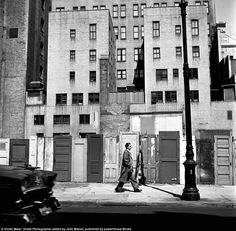Sign of life: A man walks along the sidewalk in urban Chicago in front of blocks of apartments - Vivian Maier - 1950's