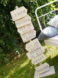 Panneau en bois sur lequel est fixé de petites pancartes directionnelles en bois…