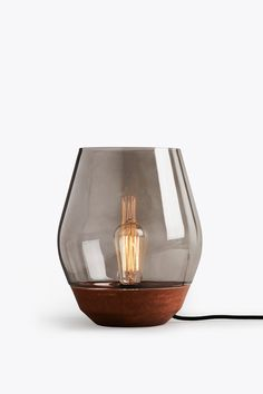 The soft reflections of the toned glass shade give the Bowl Table Lamp the  mystery and allure of a raging campfire. The smoky aura of the glass is  combined with the textured copper base, alluding to traditional lanterns,  the inspirational starting point for the design. A contemporary light with  a historical aesthetic, the soft lines create an inviting form and  comforting glow.  We recommend to use the Edison Antique E27 Light Bulb, Carbon Filaments 40W  for the best expression of the…