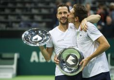 Michael Llodra, right, kisses Nicolas Mahut , left, of France as they celebrate their victory and show their trophies after their final match against Romanian Horia Tecau and Jean-Julien Rojer of The Netherlands, in the 41st ABN AMRO world tennis tournament, at Ahoy Arena, in Rotterdam, Netherlands, Sunday, Feb. 16, 2014. (AP)