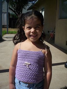 Such a cute breezy tank top for your little girl! This crocheted tank features buttons at the top of the back and is open below that to keep her back nice and cool. You choose whether to use a crocheted chain or ribbon to form straps that tie at the shoulders to make this very adjustable and there is also a sweet bow on the front center.