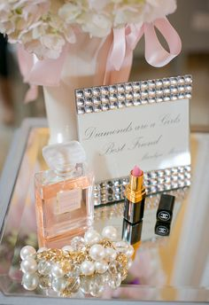 Perfume, lipstick, pearls and flowers.