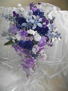 Cascade Dark Blue and Purple Wedding Bouquet with Dark Blue Roses, White and Light Purple Roses. I love this for the bouquet, except with maybe a little less purple. (And maybe a different shade of purple, too.) But the two shades of blue are perfect. Purple Wedding Bouquets, Blue Bouquet, Flower Bouquet Wedding, Floral Wedding, Cascade Bouquet, Bridal Bouquets, Wedding Themes, Wedding Colors, Wedding Decorations