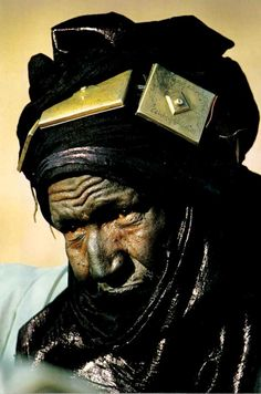 Africa | Tuareg chief, Hamadaba Muhammad of Mali displays 3 brass headband ornaments 'tcherot' on his tagelmoust/desert veil.  Arabic inscriptions on the ornaments quote passages from the Koran.  With chronic scarcity of water, some Tuareg veils must have the indigo dye pounded rather an soaked into the cloth.  Either way the dye rubs off on the wearer.  | © National Geographic, Nov. 1984. Article 'Africa Adorned'. Text & Photos Angela Fisher.