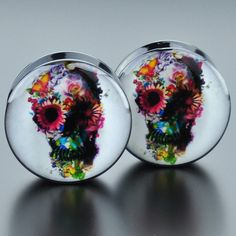 Black acrylic plugs with a picture of a skull formed by flowers. Quantity: Sold as 1 pair (2 pieces) Style: round cut plug, 1 side flat 1 side convex, screw fit back Flare: Double flare Wearable Width
