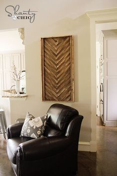 so cool.. this is made by attaching wood shim in a friendship braided pattern on to a 2'x4' piece of plywood then just add 1x2 furring strips to the sides and top to frame it.  I love it.  she use a brad nailer to nail them down, but I wonder if this could be done by just glueing the shims down?