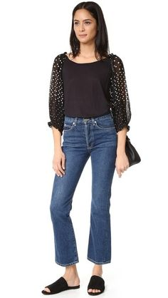 An off-shoulder Banjanan top, composed of soft, lightweight jersey and styled with puffed polka-dot chiffon sleeves. Smocked elastic at the shoulders and cuffs.
