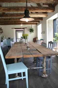 Una mesa de comedor vintage que se fabrica de madera y metal. Esta habitación tiene un look industrial.