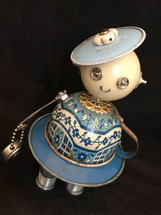 #2078 Bluebell Bot – A one of a kind found object robot sculpted by Cheri Kudja This cute little lady is made with one of the cutest tin toy teacups that I have ever worked with. It was dented pretty badly and it was a tricky one to repair but I think it has turned out great and can live on in this great robot. The rust spots and chippy paint that remain stand testament to the fact that this tin tea cup still exists. Her body is made with a vintage Wolverine toy tin tea teacup that has seen…