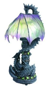 Courting Dragons Lamp.  One dragon is wound round the ivy covered castle tower base, whilst its mate is on top of the tower, with opaque green wings curled round to make the lamp shade.