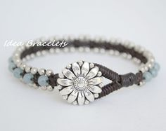 This bracelet is made of 4mm round brazilian aquamarine beads and silver beads woven together with the dark brown wax cord. I used a flower button
