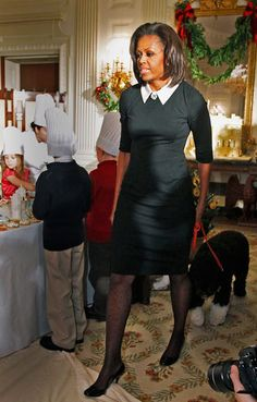 The First Lady Michelle Obama walks with Bo, the family dog, as children from military families work on crafts in the State Dining Room of the White House in Washington, DC.