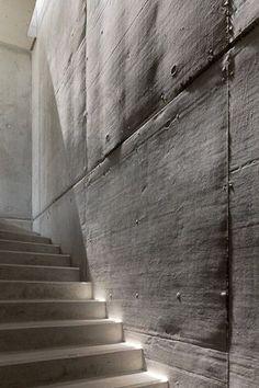 Lighting hitting the concrete wall through a thin skylight.