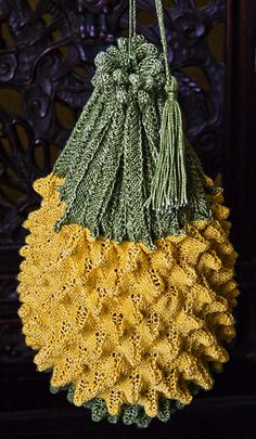 """It's a purse, shaped like a pineapple.  Now, you may never have considered knitting a purse in the shape of a pineapple; but in the mid-19th century, judging from the number of extant examples and the number of published patterns for making them, they were Just the Thing. The craze was only for pineapple bags, mind you, not for hand luggage knit in the shape of fruits generally."""