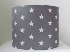 Handmade fabric lampshade with a star design Colourway: Mid Grey & White Sizes available: 20 cm wide x 20 cm high, 25 cm wide x 23 cm high, 30 cm wide x 24 cm high, 35 cm wide x 24 cm high and 40 cm wide x 25 cm high Suitable for use with lamp base or with a ceiling pendant As all shades are handmade each one is completely unique and may differ slightly to that shown in the photographs. 20 cm - perfect for a bedside table or a small to medium sized room as a ceiling fix 25 cm - a littl...