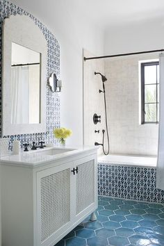 Charming white and blue Moroccan style bathroom is equipped with an ivory washstand fitted with white grill cabinet doors contrasted with oil rubbed bronze hardware and finished with a white quartz countertop.