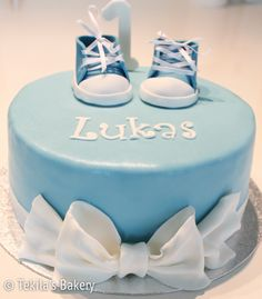 Christening cake with blue shoes and bow.