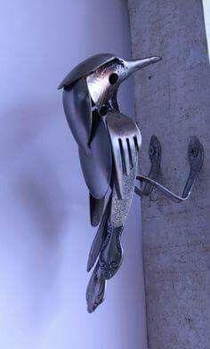 Un pájaro carpintero hecho de cucharas y tenedores metálicos