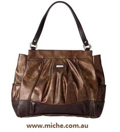 Mid Season Release! Valicity for Tote Miche Bags. Lovely and warm, with a hint of sophistication. Sound like you? This also perfectly describes the delightful Valicity Shell for Tote Miche Bags. High gloss faux leather lizard print in glimmering bronze is beautifully accentuated by soft front pleats and dark brown piping detail. Side pockets.