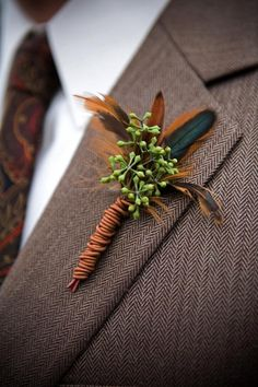 Seeded Eucalyptus backed with feathers results in a boutonniere that is sophisticated and masculine. Love it! pecock feathers?