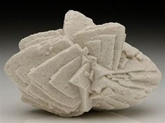 A classic French specimen from Bellecroix, Fontainebleau of rhombic Calcite crystals in a cluster formation of offset parallel growth. Crystal Classics Minerals