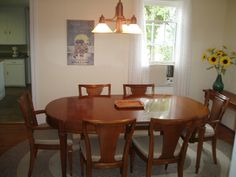 Dining Room Furniture Ideas for White Small Space with Ellipse Shaped Brown Wood Dining Tables on the Gray Soft Carpet and Simple Wood Brown Dining Chairs that have Soft Gray Fabric Seat Cushions also Simple Wood Pendant Lamp that have Three Shades