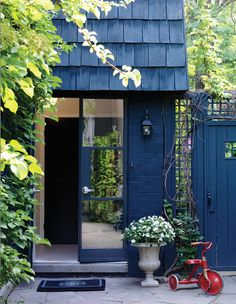 Painting the entire façade a deep blue-black unifies the brick, shingled roof, fence and lattice, and creates a dramatic backdrop for bright green foliage. See more of chef Trish Magwood's home in ou