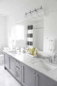 source: AM Dolce Vita  Gray Yellow Bathroom, Bianco Carrara floor, Vanity in Benjamin Moore Pigeon Gray, Bianco Statuario countertop, Kohler Fairfax lavatory faucets, Pottery Barn Mercer sconce, Benjamin Moore Chantilly Lace, West Elm Stripe Shower Curtain in Feather Gray, Stacked 4x16 white subway tiles Carrara border