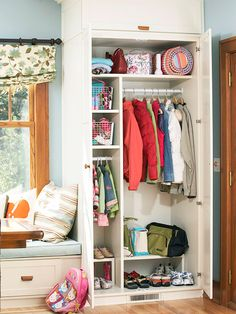 Tall cabinets make the most of this hall space inside a back door, which opens into a kitchen and breakfast nook. Inside the cabinets, there's plenty of space for kids to stash coats and scarves. The cabinet door neatly conceals everything from sight.