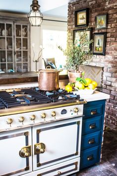 Textured brick is the perfect backdrop for blue cabinetry accented perfectly with polished brass accents.