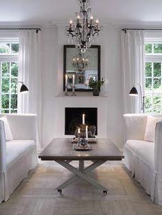 white sofas. white walls. white drapes. brown coffee table.