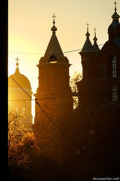 taivasalla.net - Under the Open Sky - May 2011, Helsinki: The Lutheran Cathedral and the Uspenski Cathedral in the golden glow of the setting sun. Photo taken from Kruunuvuorenkatu street in the district of Katajanokka. Finland