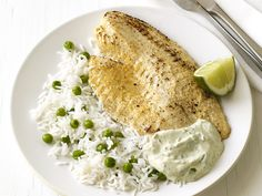 "(40 minute) tilapia masala with rice. need: 1 c basmati rice, 1/2 c frozen peas, 3/4 plain yogurt, 1 sm garlic clove, 1 1"" piece of ginger peeled and chipped, 1 T fresh lime juice, lime wedges for serving, 1/4 t ground cumin, 1/4 t cayenne pepper, 4 6oz tilapia filets, 2 T unsalted butter, 1 T cilantro or mint."