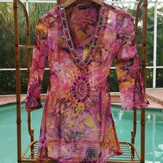 """Sheer, flirty & fun top Sheer top, labeled M but fits like a Small (4).  100% viscose.  14"""" across shoulders.  28"""" at ribcage, 32"""" at waist,  6"""" slits at sides for room at hips.  Upper arm is max 10"""" around, then opens just above the elbow with a 9"""" slit.  Top is about 29"""" shoulder to hem.  Ornamented with hand-sewn pieces of pink, purple & gold to match fabric of the top.  A couple of small beads are missing & a few are loose, easy to fix.  Worn 1x to a party with a cute pair of shorts and…"""