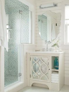 Expand a small bathroom's utility by designing a walk-in shower that provides a solid wall or walls for placing vanities or tubs. Seemingly an extension of the bathroom's board-clad walls this knee wall accommodates a shallow vanity with a mirrored door. White painted walls the shower's glass enclosure and tiled walls and reflective surfaces encourage light to move around the space causing the small bathroom to appear roomier.